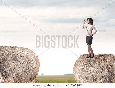 Young businesswoman standing on edge of rock mountain