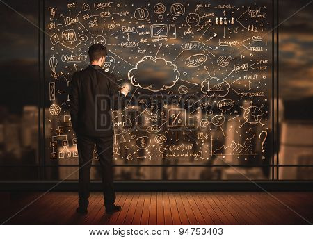 Businessman drawing business plan on glass window with bokeh background
