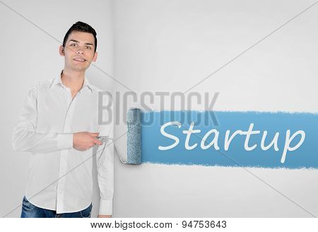 Young man painting Startup word on wall