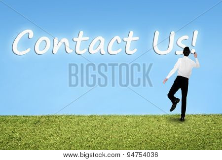Business man writing on sky Contact us word