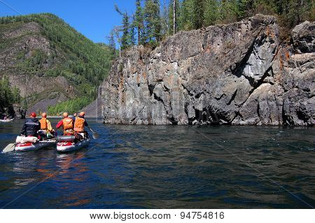 Team of people on an inflatable catamaran raft on a river canyon.