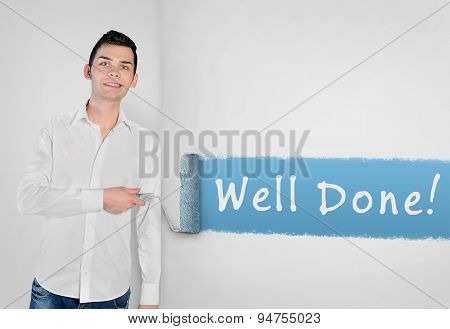 Young man painting Well done word on wall