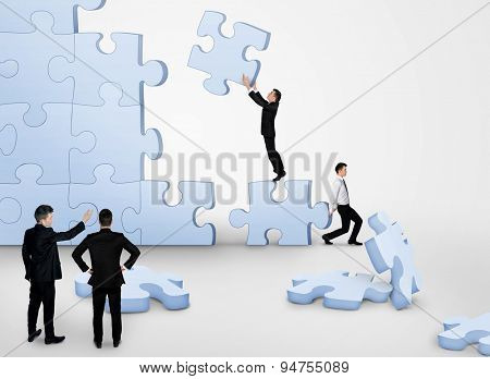 Business team building puzzle pieces together