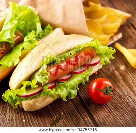 Hot dog. French fries, Grilled hot dogs with mustard and ketchup on a picnic wooden table. Sandwich, Hotdog
