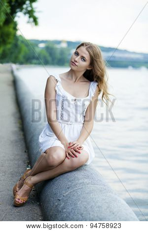 Portrait of young blonde woman sitting on stone