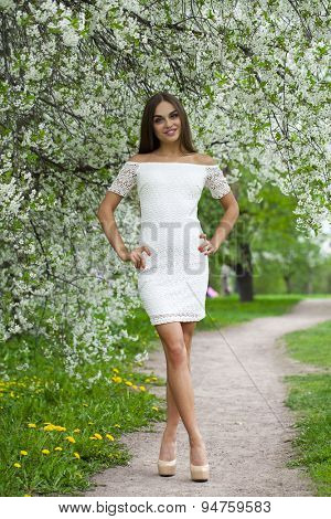 Beautiful young brunette woman in white dress walking in spring park