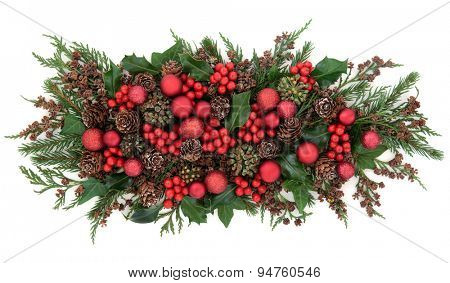 Christmas flora with red bauble decorations, holly, ivy and winter greenery over white background.