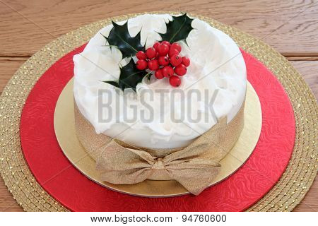 Traditional christmas cake with holly and gold bow.