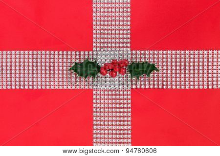Christmas diamond bling and holly gift wrapping over red paper background.