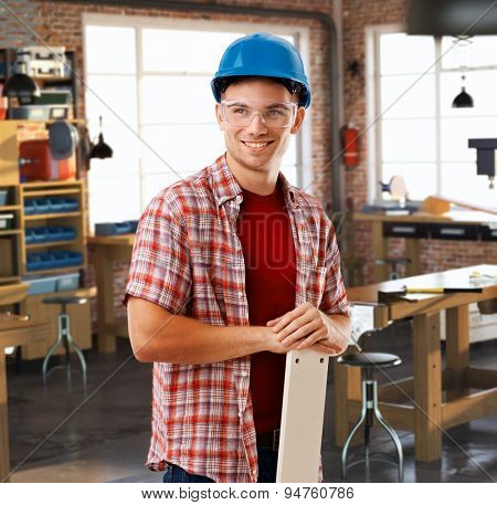 Happy casual handyman with hardhat and safety goggles standing at workshop. Smiling.