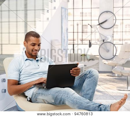 Relaxed casual afro american man browsing online with laptop computer at bright loft apartment. Sitting, barefoot, smiling, looking at screen.