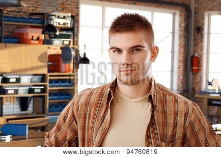 Portrait of confident casual young bristly caucasian student at DIY workshop. Looking at camera.