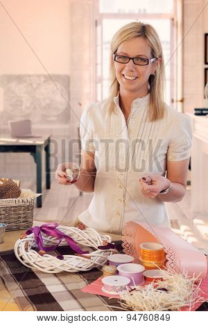 Happy casual caucasian blonde mid adult woman making valentine day wreath at home. Smiling, wearing glasses, looking at camera, standing at table, do it yourself, gift, present.