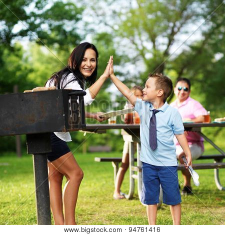grilling mom giving high five to son at picnic