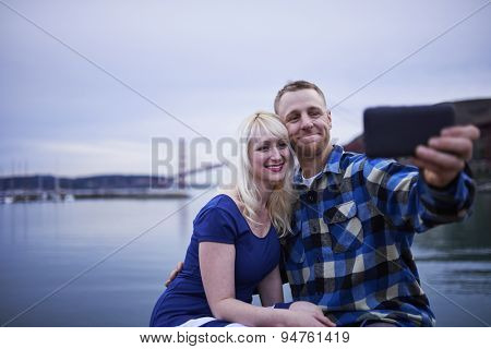 couple sitting by water front beside golden gate bridge taking selfies together