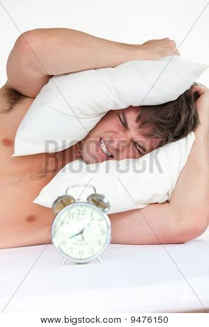 Angry Man Woken Up By His Alarm Clock Putting Pillow On His Head
