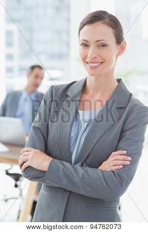 Smiling businesswoman with colleagues behind at office