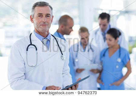 Doctor looking at camera while his colleague discussing in medical office