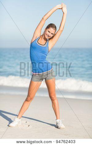 Beautiful fit woman stretching her arms at the beach