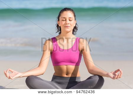Fit woman doing yoga beside the sea at the beach