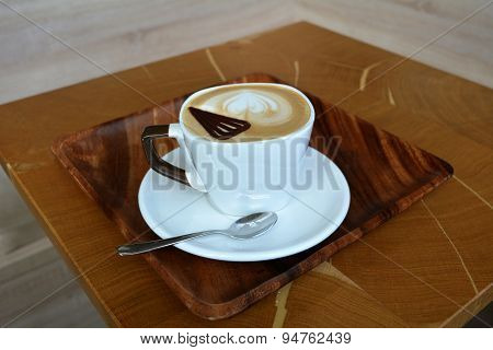 Cup of foamy cappuccino on a wooden table