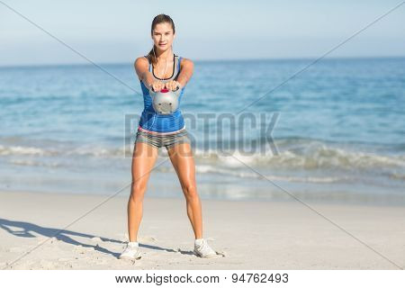 Beautiful fit woman holding dumbbells at the beach