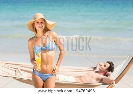 Pretty woman looking at camera while her boyfriend relaxing on the hammock at the beach