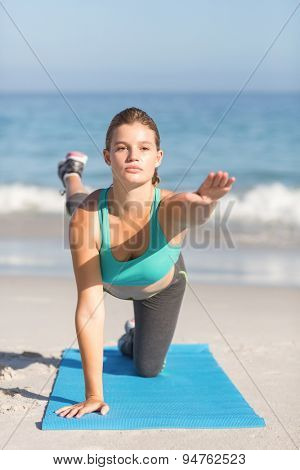 Fit woman stretching on exercise mat at the beach