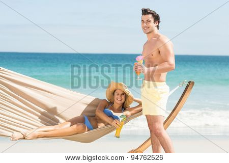 Happy couple holding cocktail at the beach