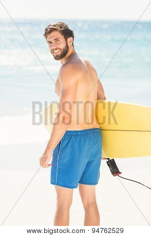 Wear view of handsome man holding surfboard at the beach