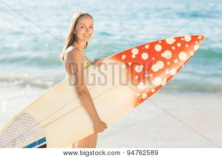 Pretty brunette holding surf board at the beach