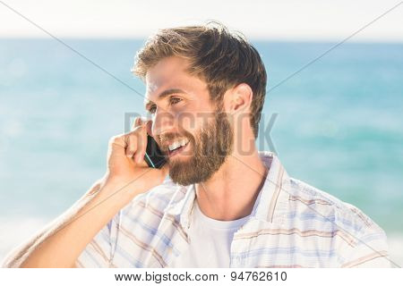 man using his phone on the beach
