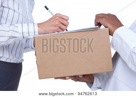 Businesswoman signing papers for package on white background
