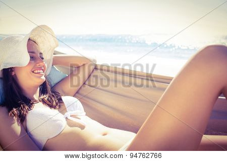 Brunette relaxing in the hammock and smiling at camera at the beach