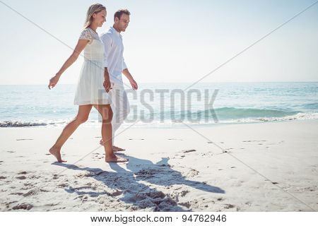 Romantic casual young couple holding hands and standing at the beach