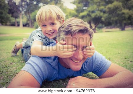 Happy father and his son smiling at camera on a sunny day