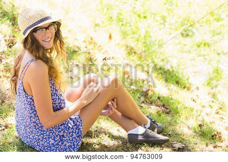 Pretty brunette relaxing in the grass on a sunny day