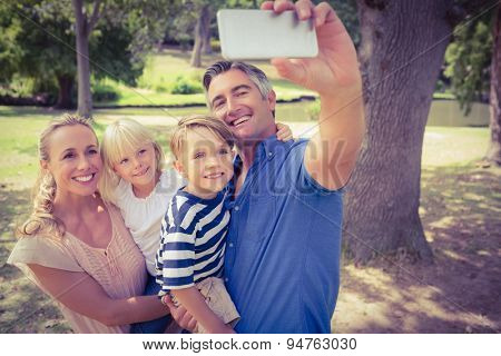 Happy family taking a selfie in the park on a sunny day