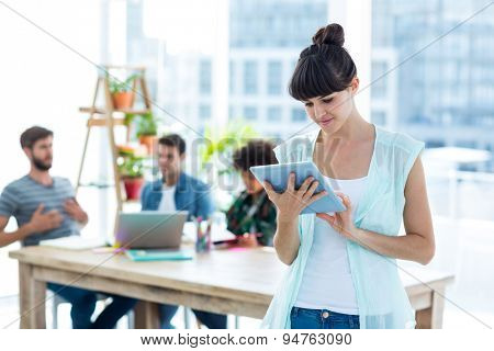 Smiling young businesswoman using tablet in the office