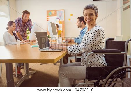 Creative casual businesswoman in wheelchair in the office