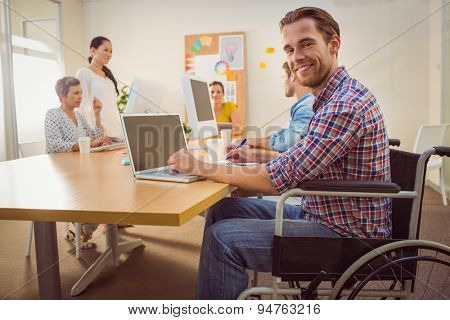 Portrait of creative casual businessman in wheelchair in the office