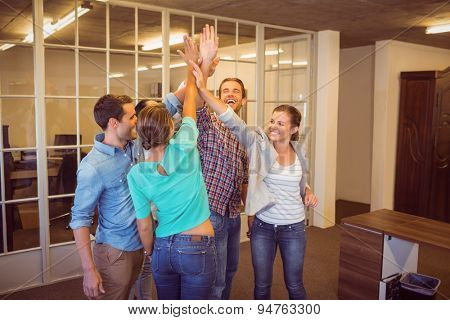 Creative business team raising their hands at the office