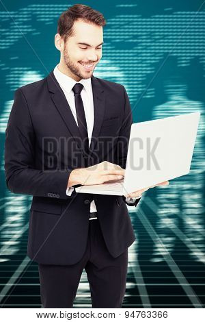 Smiling businessman standing and using laptop against white silhouettes on black background