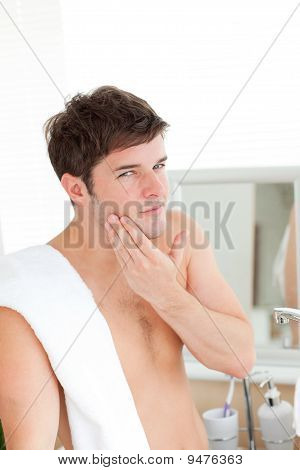 Young Man Putting Aftershave In The Bathroom
