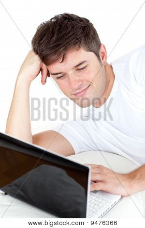 Thoughtful Man Using His Laptop Lying On The Ground
