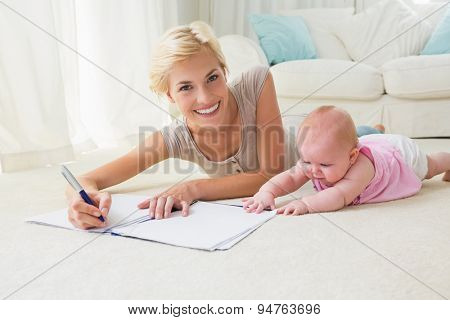 Smiling blonde mother with her baby girl writting on a copybook at home in the living room