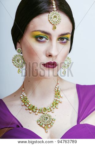 young pretty caucasian woman like indian in ethnic jewelry close up