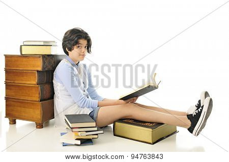 At attractive young book-loving teen looking up at the viewer from the one she's reading.  She is surrounded by books.  On a white background.