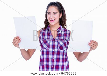 Pretty brunette looking at paper sheet on white background