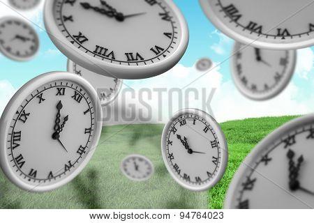 Clocks against green field under blue sky